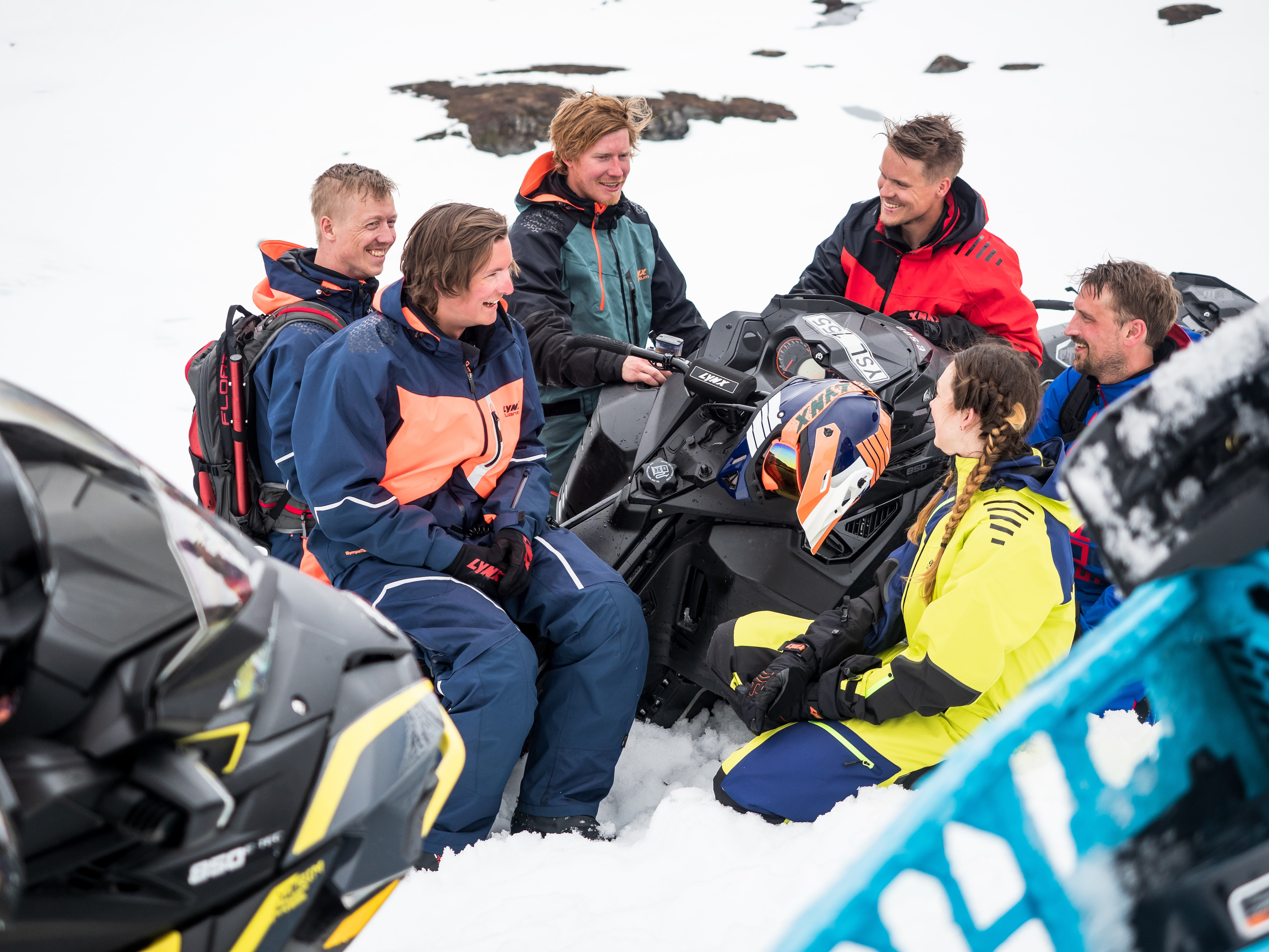 Group of friend discussing around their Lynx snowmobiles