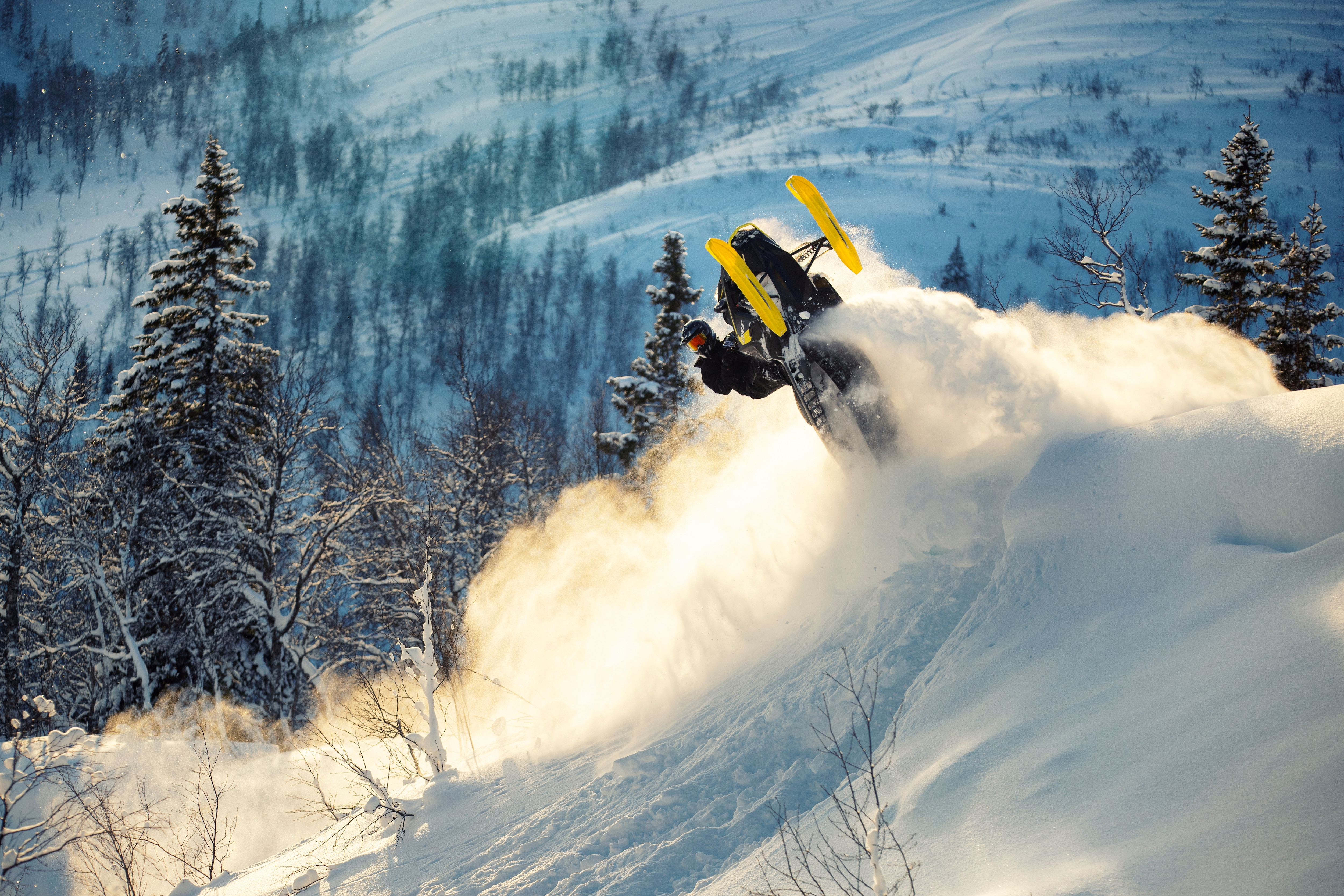 man jumping in snow with Lynx snowmobile