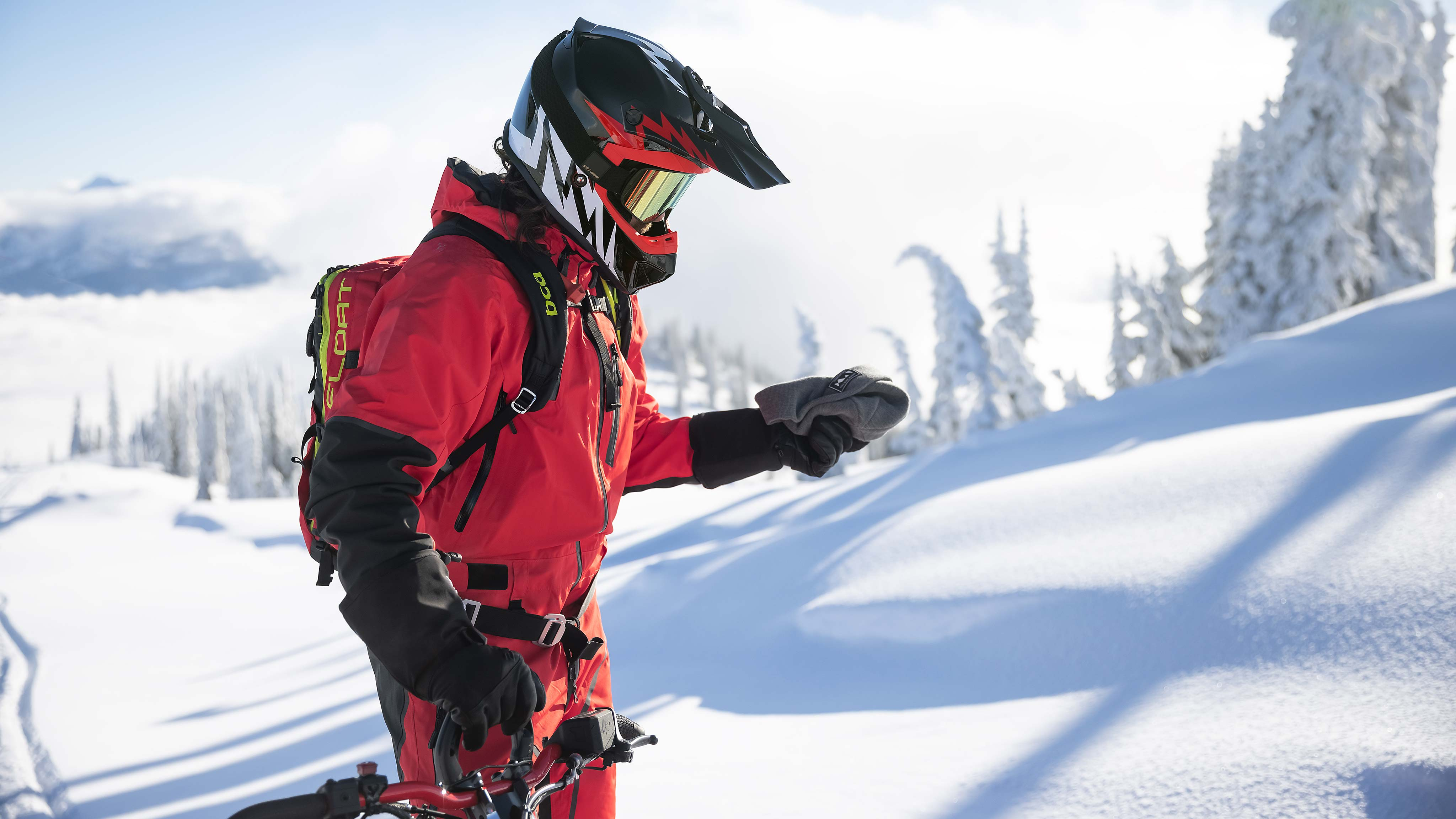Lynx snowmobile rider with helmet and one-piece suit on terrain