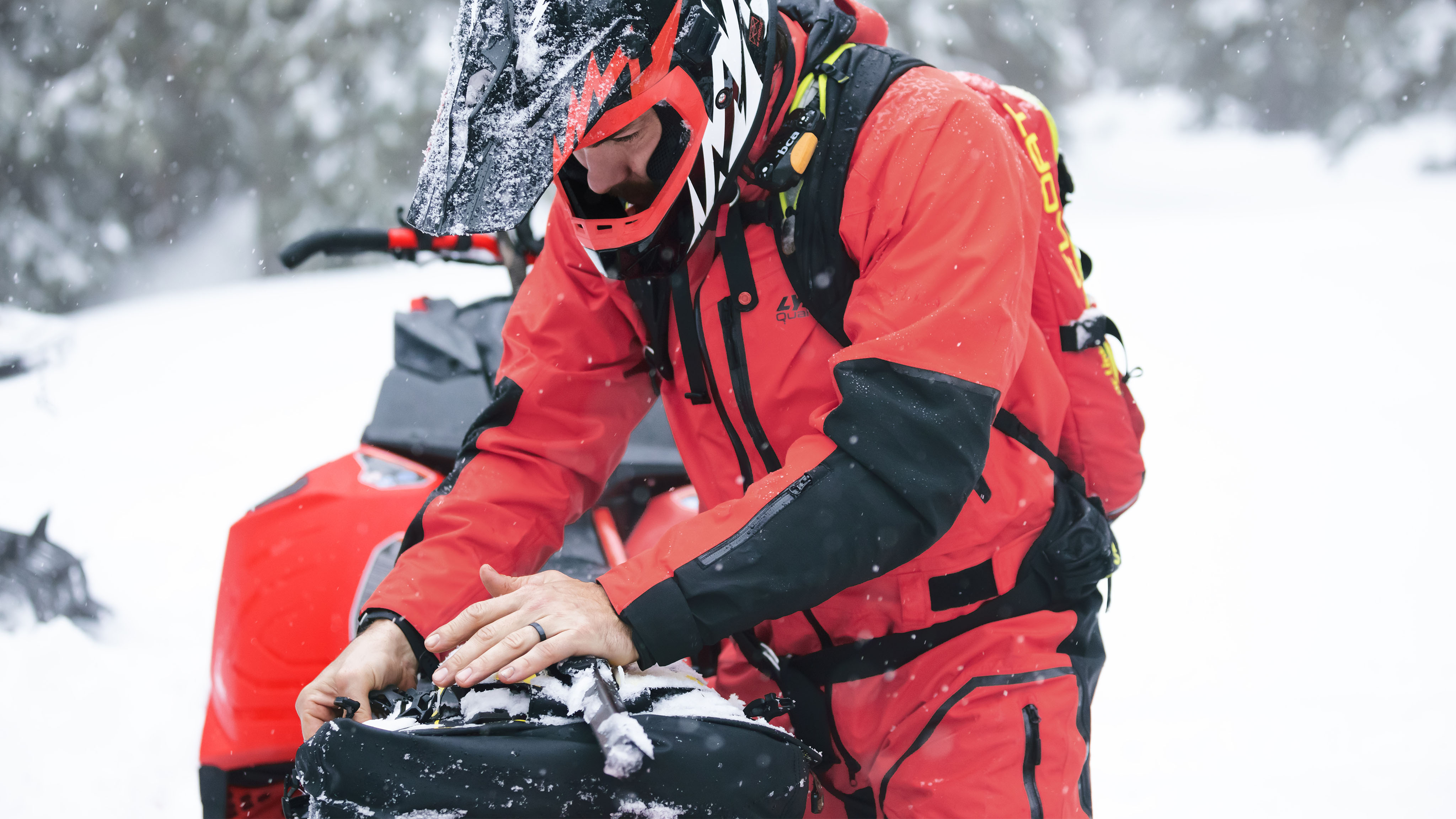 Man wearing Lynx Apparel and preparing a snowmobile ride