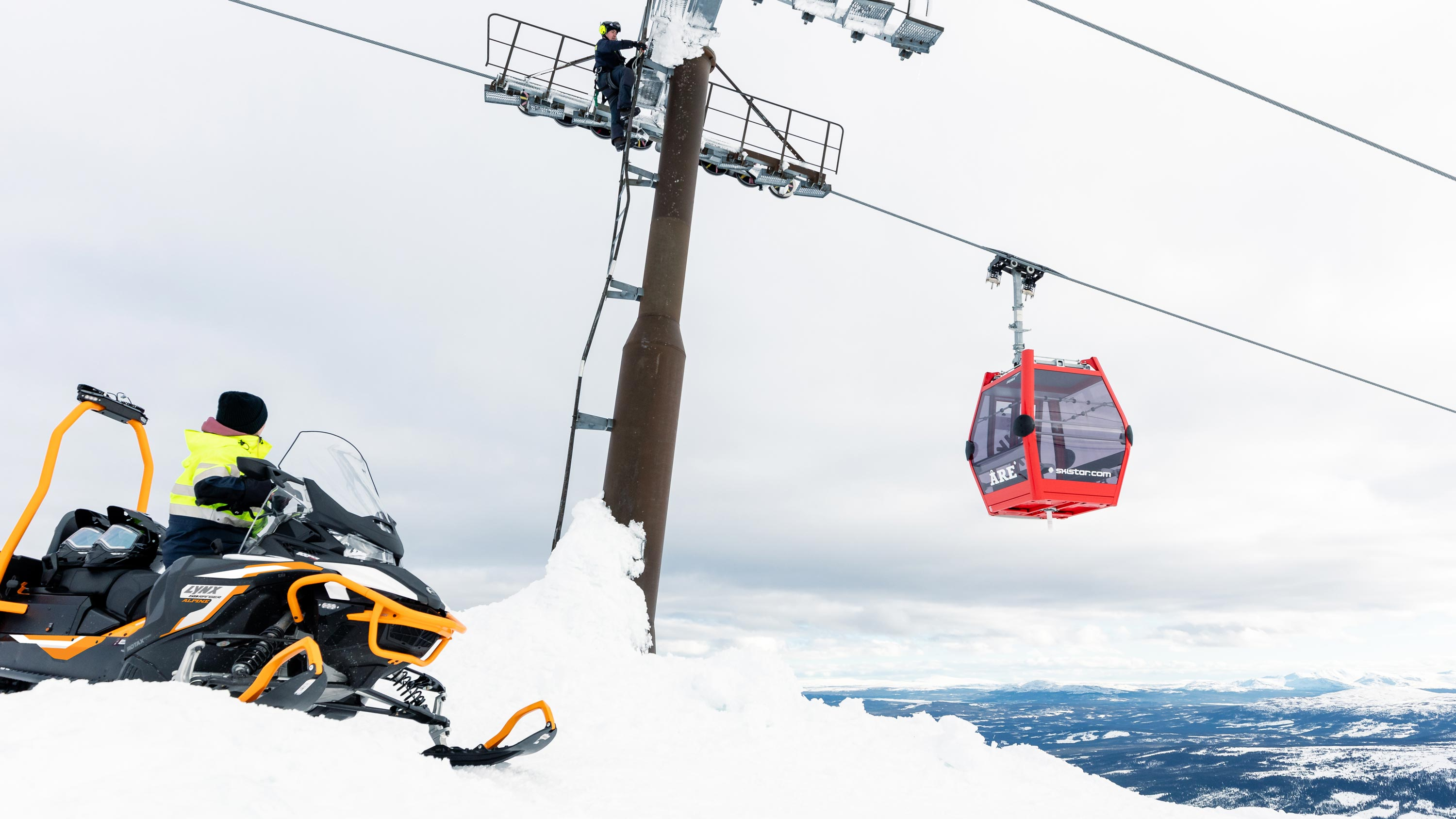 Person riding Lynx 59 Ranger snowmobile in a ski resort