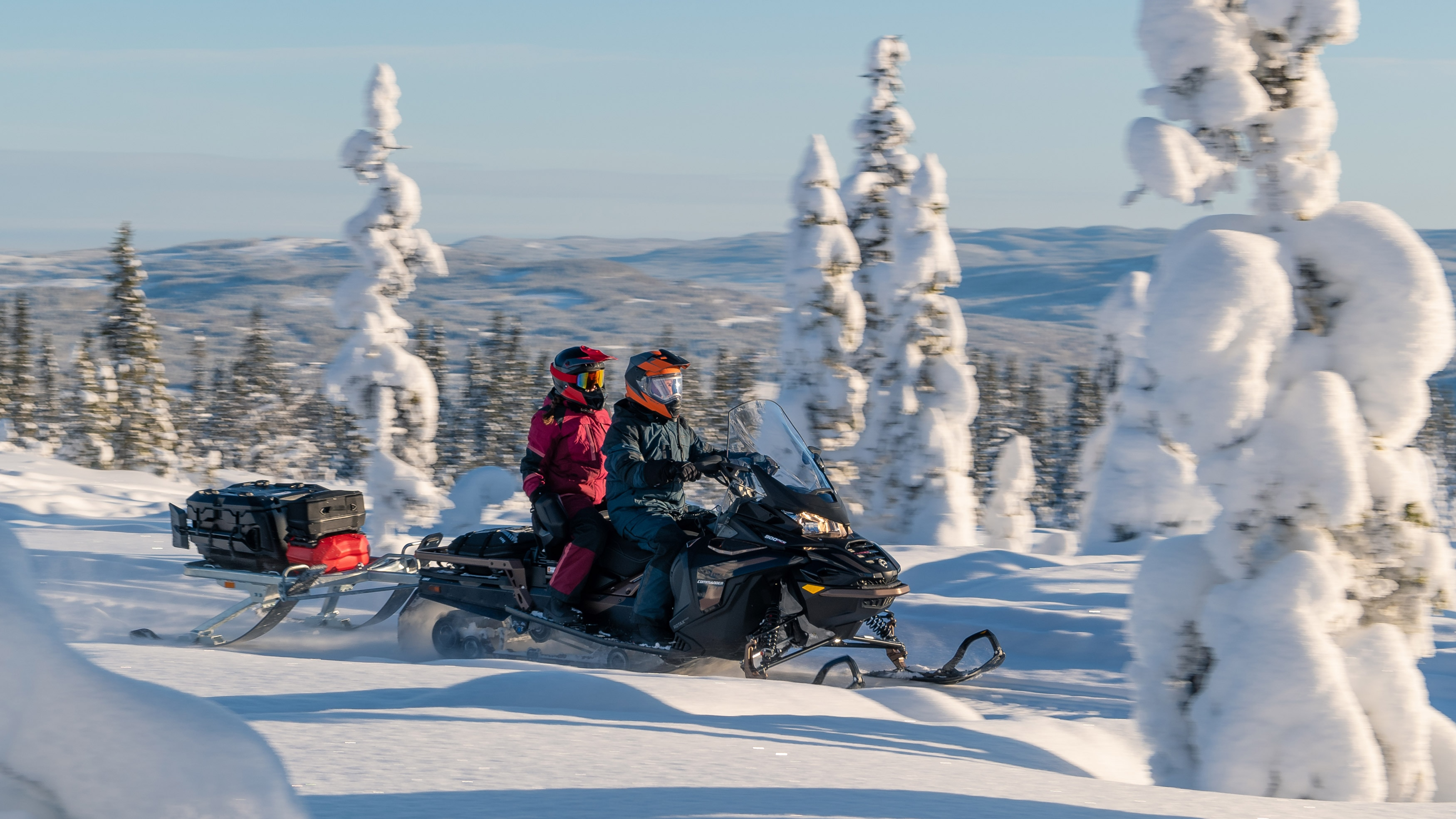 Lynx Commander Grand Tourer snowmobile two up riding on trail in snowy forest.